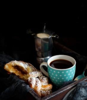 暗い背景にクロワッサンとコーヒーのカップをクローズアップ