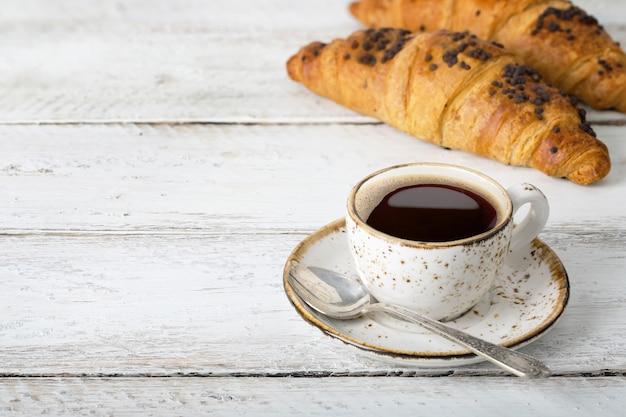 Чашка кофе с круассанами на белом деревянном столе, вкусная выпечка, деревенский, ремесло