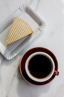 大理石のテーブルにデザートとコーヒーのカップ。コーヒーの日。白い背景の上の朝食。ケーキと温かい飲み物。アロマコーヒーの上面図。食べ物とブラックコーヒー。カフェで朝食。食糧の日