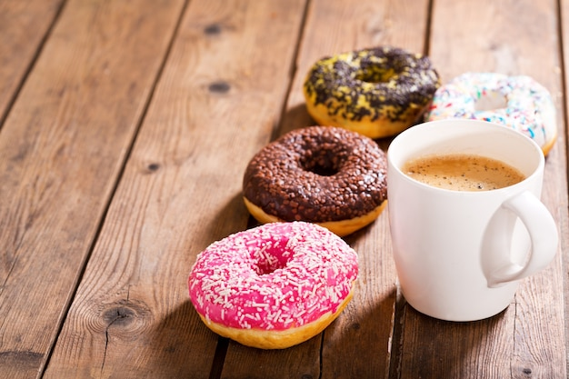 木製のテーブルにドーナツとコーヒーのカップ