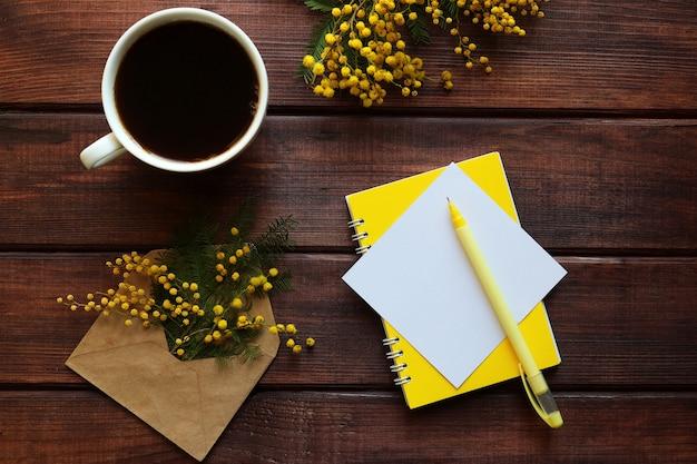 空の紙の空白と木製のテーブルの上のペンとコーヒーのカップ