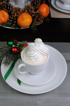 クリスマステーブルの受け皿にモミの枝とコーヒーのカップ