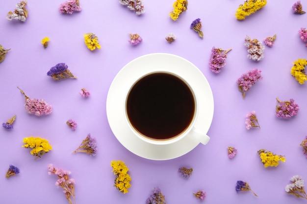 Чашка кофе с цветами на фиолетовой поверхности