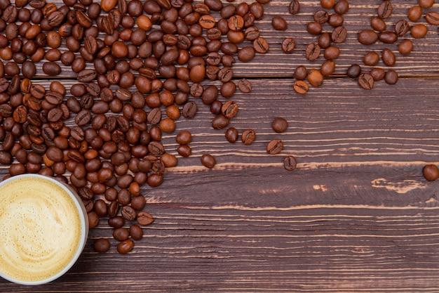 Чашка кофе с пеной на дереве и свободное место для текста. коричневый деревянный фон