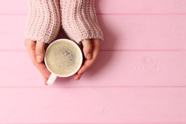 Чашка кофе с пенистой в женских руках на деревянном столе, вид сверху