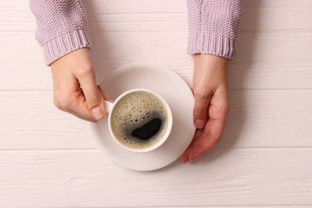 나무 탁자 위에 있는 여성의 손에 거품이 일고 있는 커피 한 잔
