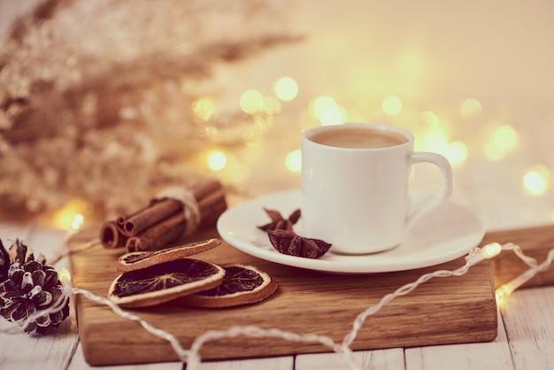 ガーランドライトとテーブルの装飾とコーヒーのカップ。居心地の良いホームコンセプト