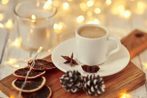 テーブルの上のろうそくや装飾を燃焼ガーランドライトとコーヒーのカップ。居心地の良いホームコンセプト