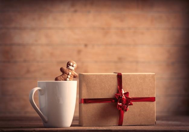 ジンジャーブレッドマンと木製のテーブルの上のクリスマスプレゼントとコーヒーのカップ