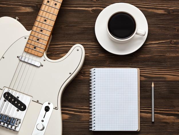Чашка кофе с гитарой и блокнотом
