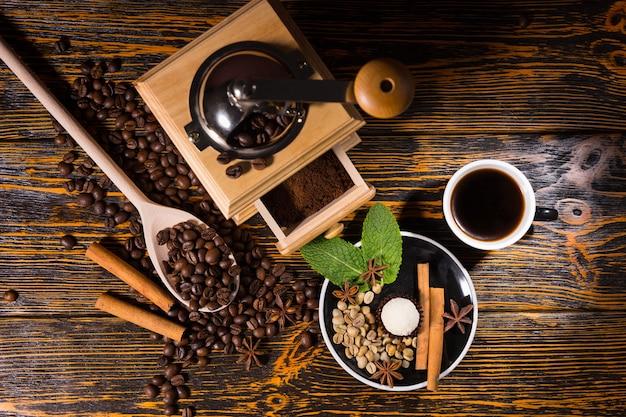 ハンドグラインダー、豆、スパイスとコーヒーのカップ
