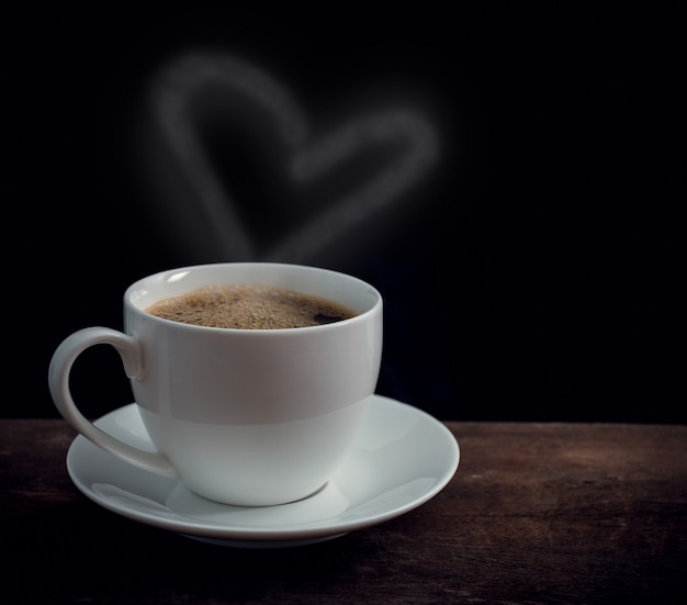 Чашка кофе с сердцем в форме дыма на старом деревянном столе
