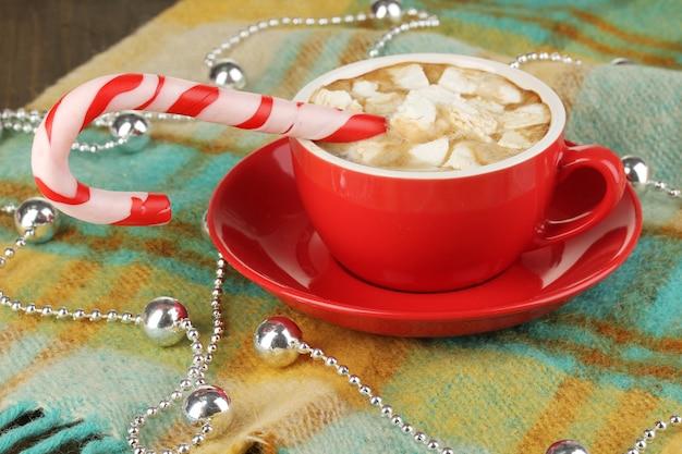 格子縞のクローズアップにホリデーキャンディーとコーヒーのカップ