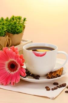 Чашка кофе с помадой и бобами герберы, палочки корицы на деревянном столе