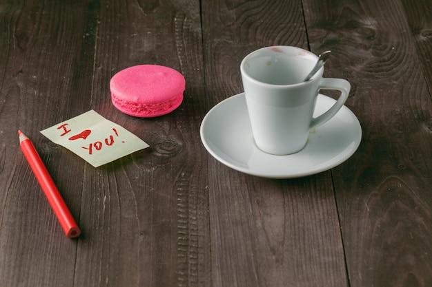 口紅のマークが付いた一杯のコーヒーとテーブルの上の「愛しています」のクローズアップ