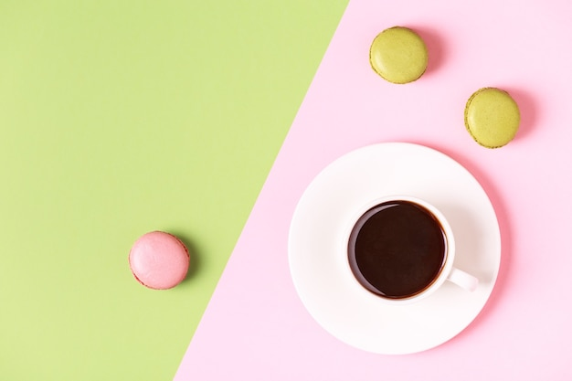 パステルカラーの背景にマカロンとコーヒーのカップ