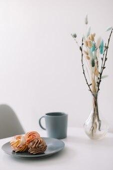 Чашка кофе с зефиром и цветами на столе романтическое утро