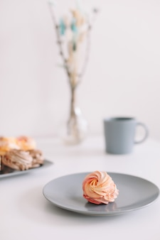 Чашка кофе с зефиром и цветами на столе