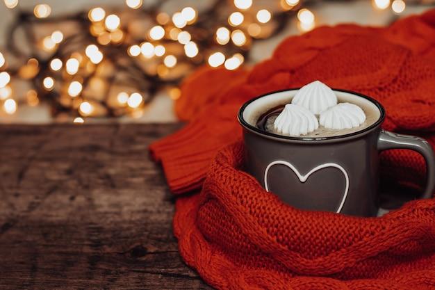 木製のテーブルにマシュマロとコーヒーのカップ。美しいボケ