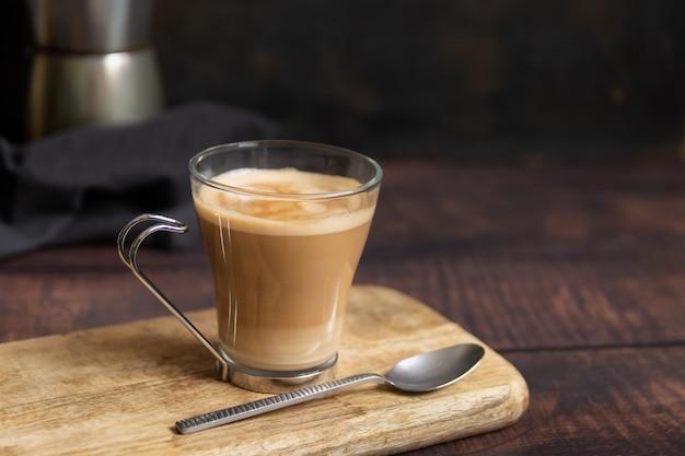 木製のテーブルと背景のイタリアンコーヒーポットにミルクと小さじ1杯のコーヒー