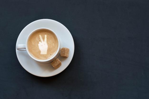 Чашка кофе с молоком, тростниковым сахаром и знаком победы на темном фоне. вид сверху. копировать пространство