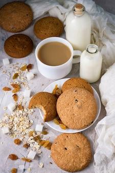 白いカップに牛乳とコーヒーのカップ、牛乳のボトル、オートミールクッキー、オートミール、軽い表面にレーズン。朝食の様子。フラットレイとトップビュー