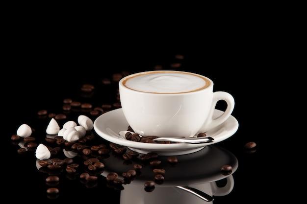 黒の背景に牛乳とコーヒーのカップ。反射のあるテーブルで作られたホットラテまたはカプチーノ