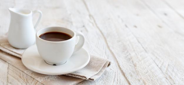木製の背景にミルクとコーヒーのカップをクローズアップ
