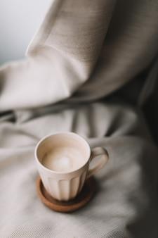 Чашка кофе с молоком на бежевом пледе. плоская планировка, вид сверху, натюрморт, утренний завтрак. концепция комфорта, уюта и тепла. фото в светлых пастельных тонах