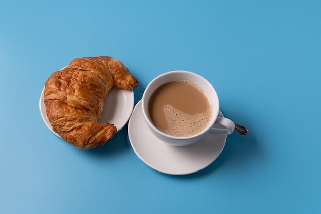 Чашка кофе с молоком на синем фоне, с круассаном, копией пространства для текста.