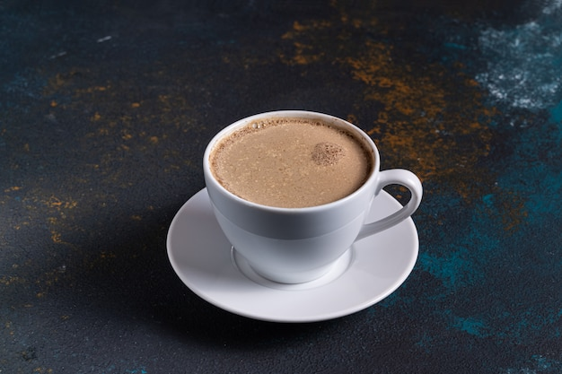 Чашка кофе с молоком на синем столе, вид сверху.
