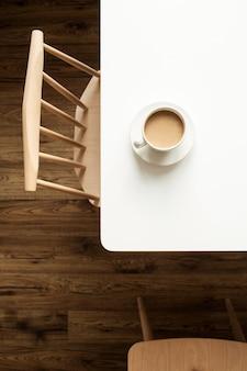 디자이너 의자와 나무 바닥 근처 흰색 테이블에 우유와 커피 한잔
