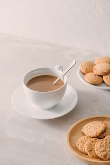 明るい石の背景にミルクまたはクッキーとカプチーノとコーヒーのカップ