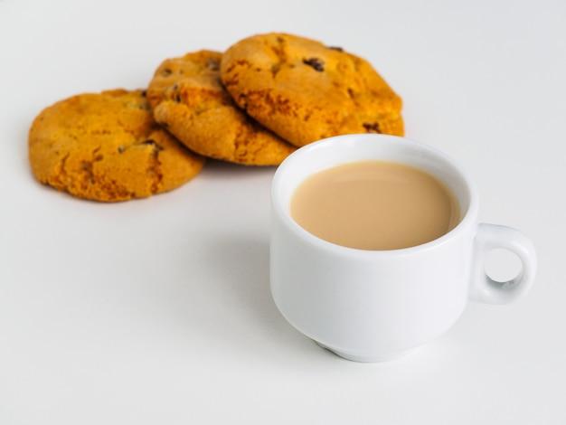 Чашка кофе с молоком. печенье с изюмом.