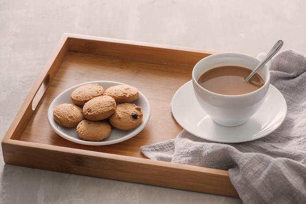 明るい石の背景にクッキーとミルクとコーヒーのカップ