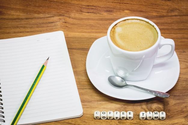 Чашка кофе с записной книжкой и карандашом
