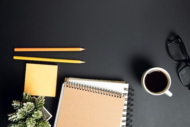 Чашка кофе с блокнотом и карандашами с бумагой на столе