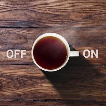 Чашка кофе с включением и выключением на пустой старой коричневой деревянной поверхности текстуры