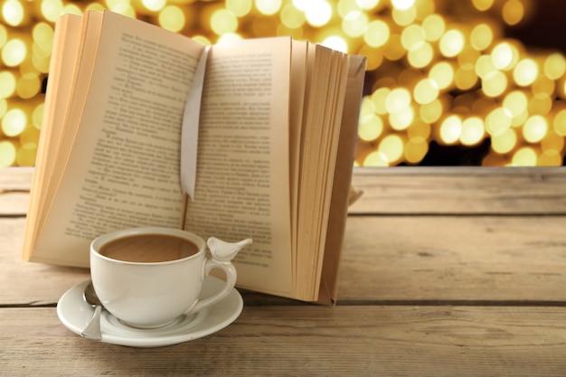 明るい表面に開いた本とコーヒーのカップ