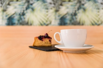 Cup of coffee with pastry on wooden surface
