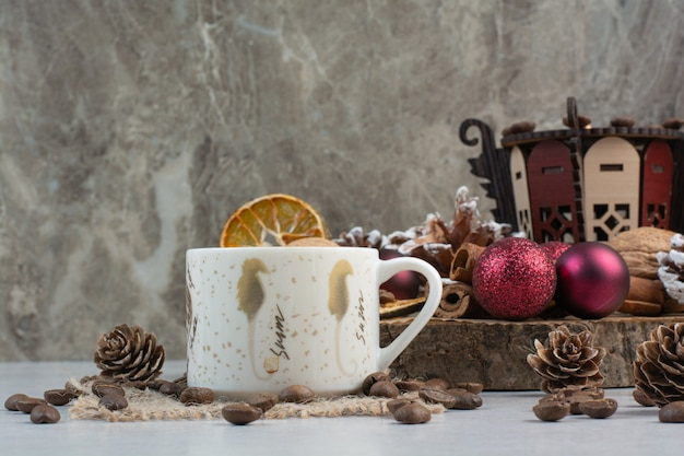 木の板に松ぼっくりとクリスマスボールとコーヒーのカップ。高品質の写真