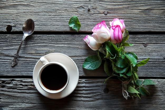 赤いバラと木の背景の上のコピースペースとコーヒーのカップ。母の日、女性の日、バレンタインデー、または誕生日の朝食。ホットドリンク、花