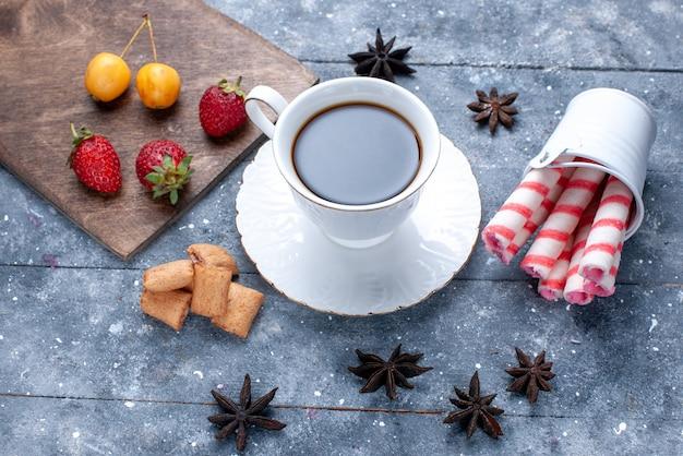 明るい机の上の赤いイチゴクッキーピンクスティックキャンディー、クッキーキャンディーコーヒービスケットベリーとコーヒーのカップ