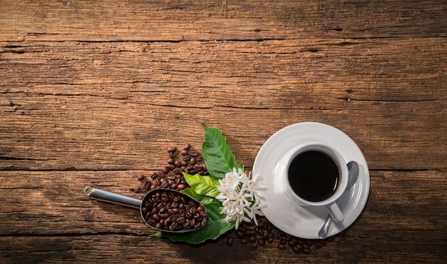 濃厚な焙煎コーヒー豆と木の背景にコーヒーの花とコーヒーのカップ