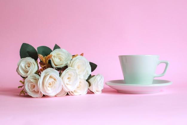 ピンクの背景に分離されたバラとコーヒーのカップ