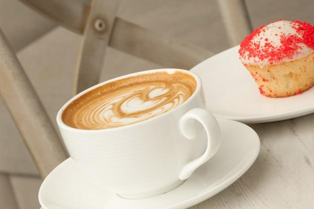 椅子の背景にテーブルの上に受け皿とケーキとコーヒーのカップ