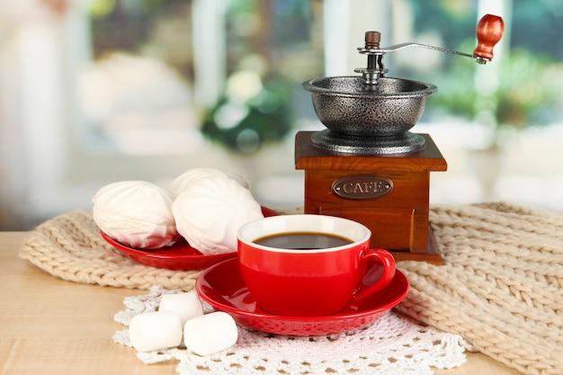Чашка кофе с шарфом и кофейная мельница на столе в комнате