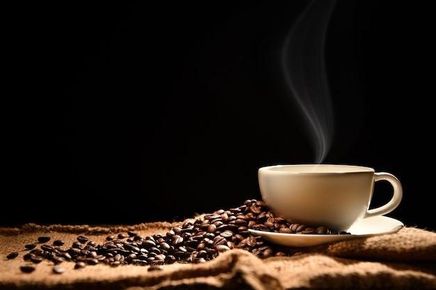 木製の背景に煙とコーヒー豆とコーヒーのカップ