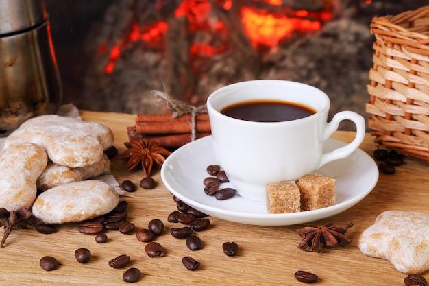 불타는 벽난로 배경에 향신료와 케이크가 든 커피 한 잔