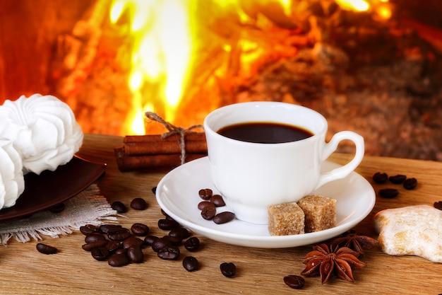 불타는 벽난로 배경에 향신료와 마시멜로가 든 커피 한 잔